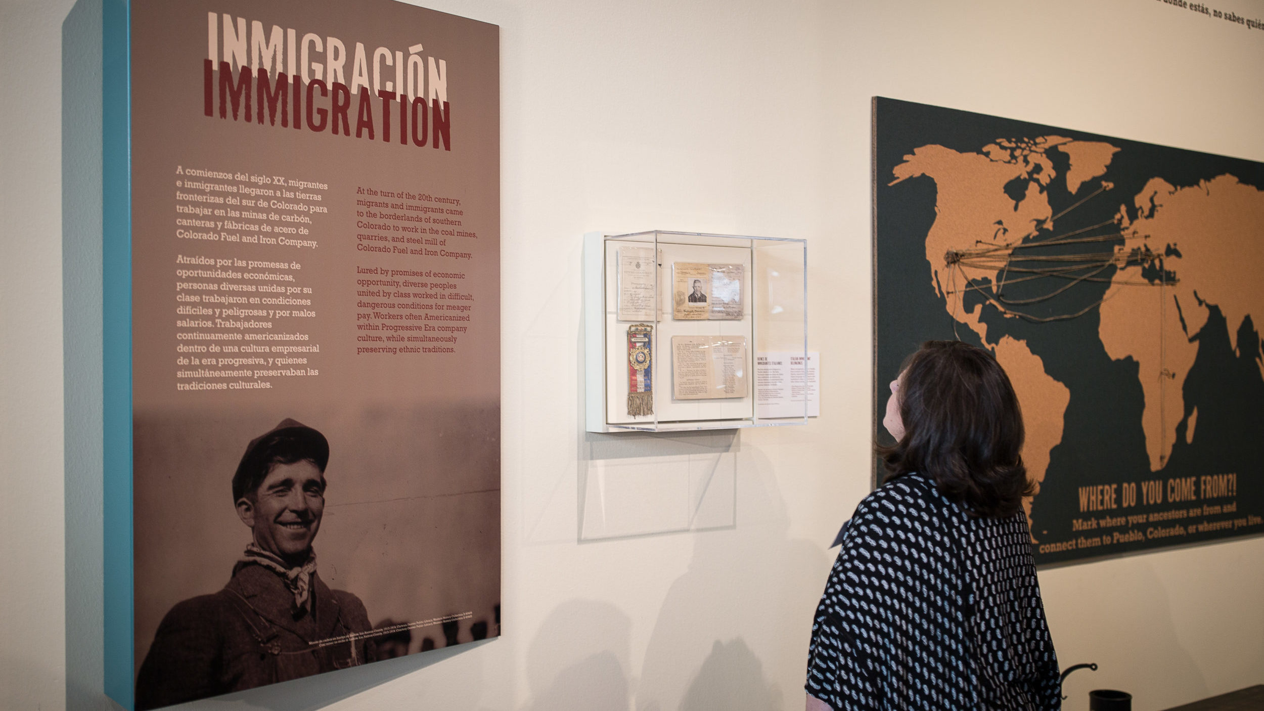 "A visitor in a gallery reading a placard that says ""Immigration"" in English and Spanish."