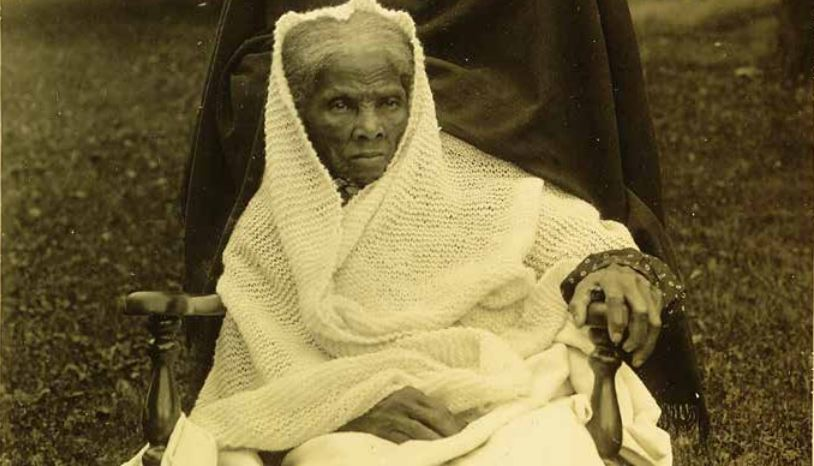 Harriet Tubman sits in a wheelchair wrapped in a knitted blanket.