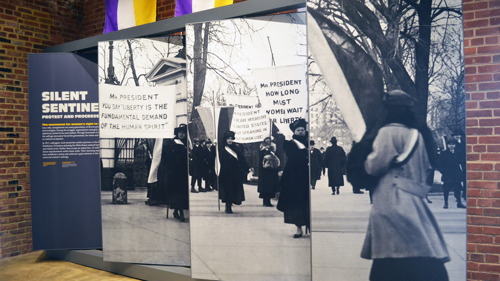 "A panel display titled ""Silent Sentinels"" shows suffragists protesting in front of the White House with signs."
