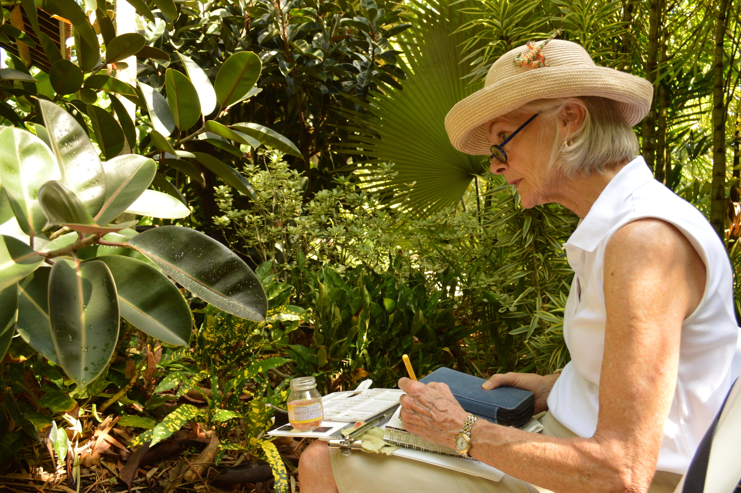 A person looking at a plant with concentration while holding a notebook and drawing implement