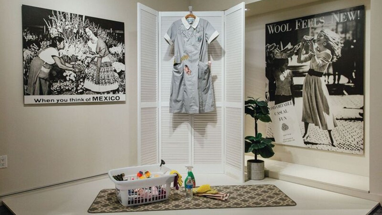 A gray maids uniform hangs from a louvered folding screen with various cleaning products laid out in a laundry basket and on the floor in the Nanny exhibition.
