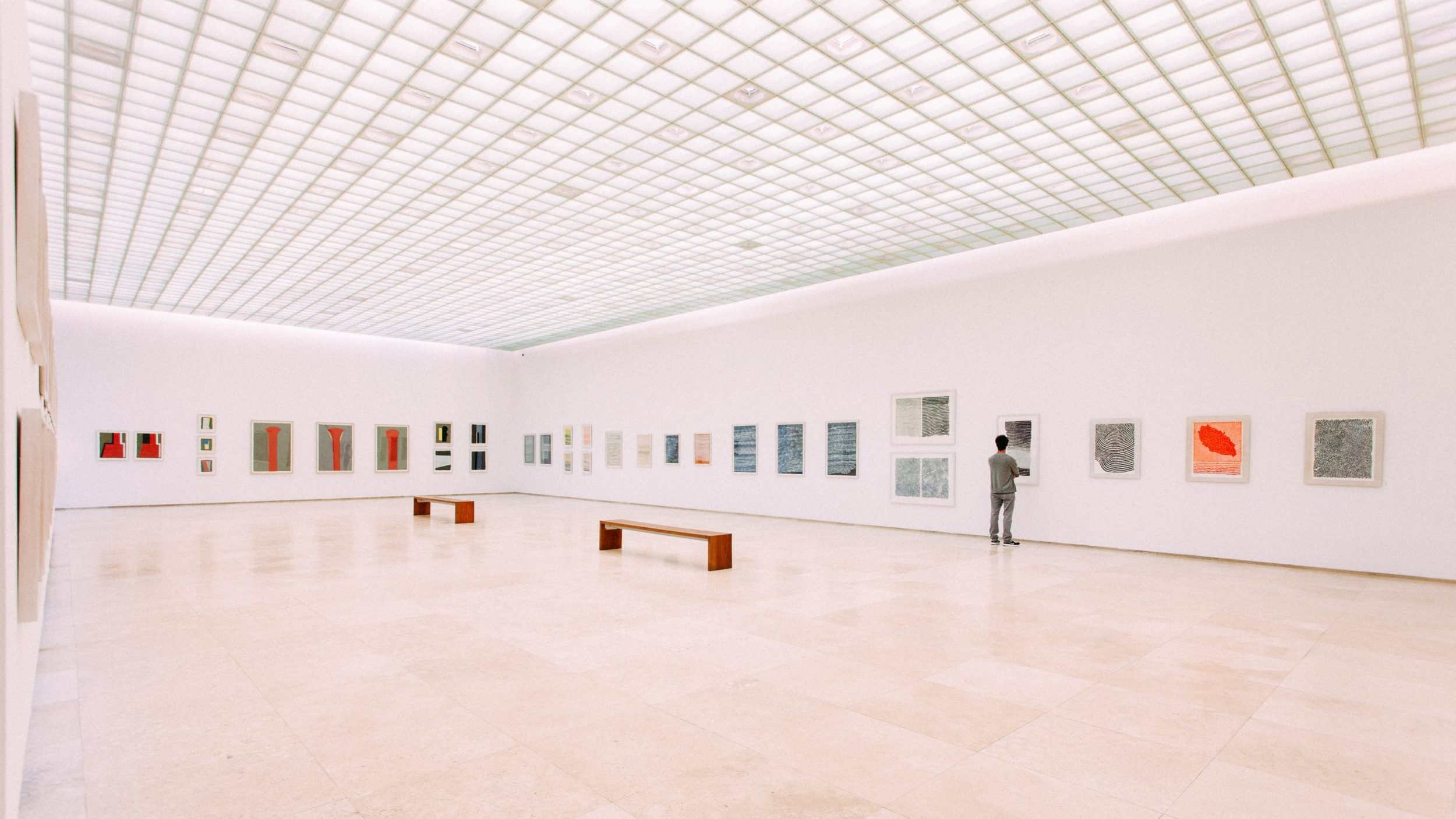 Wide shot of a museum gallery with paintings on display