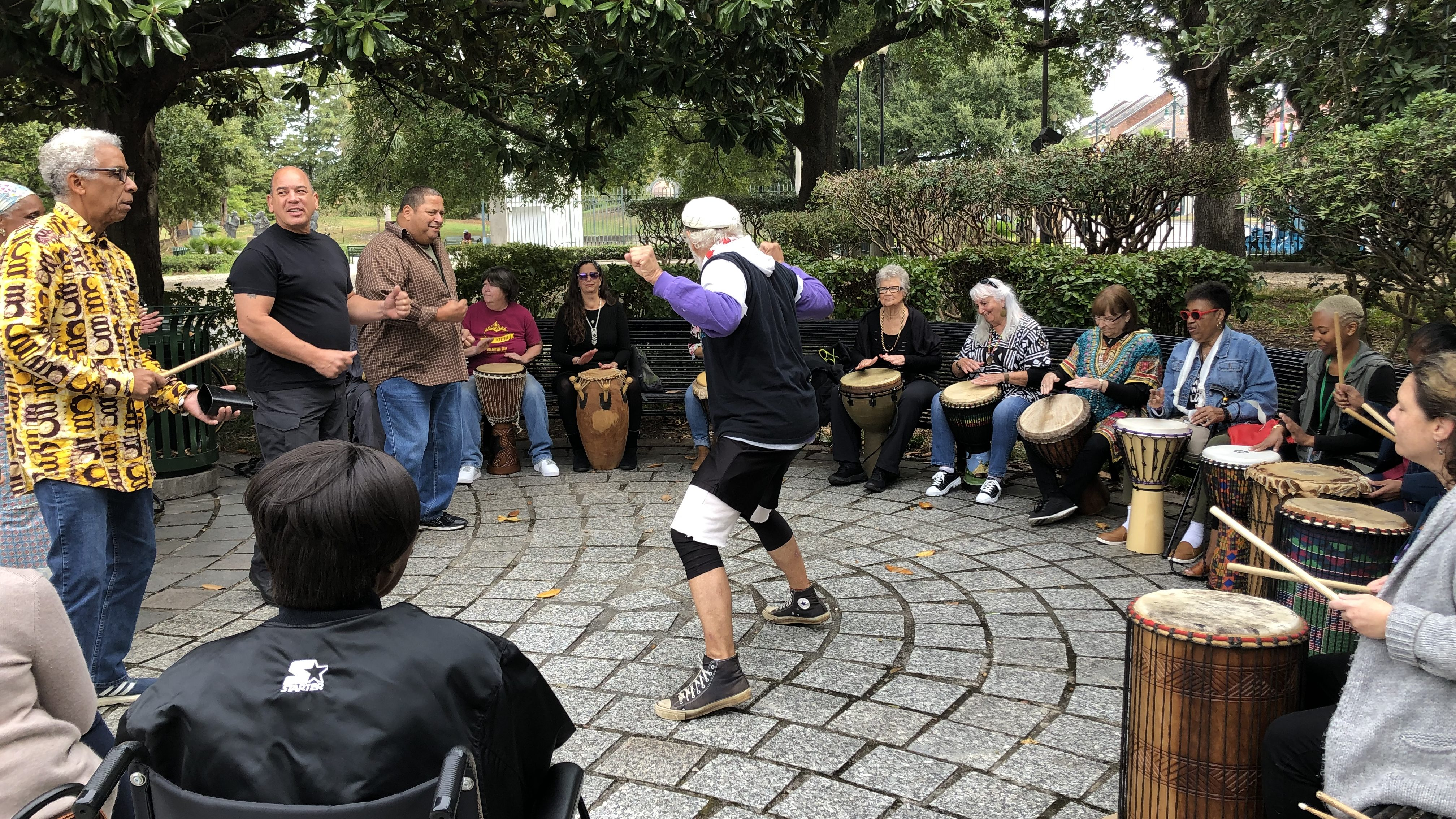 People sitting around in a drum circle while others dance in the middle