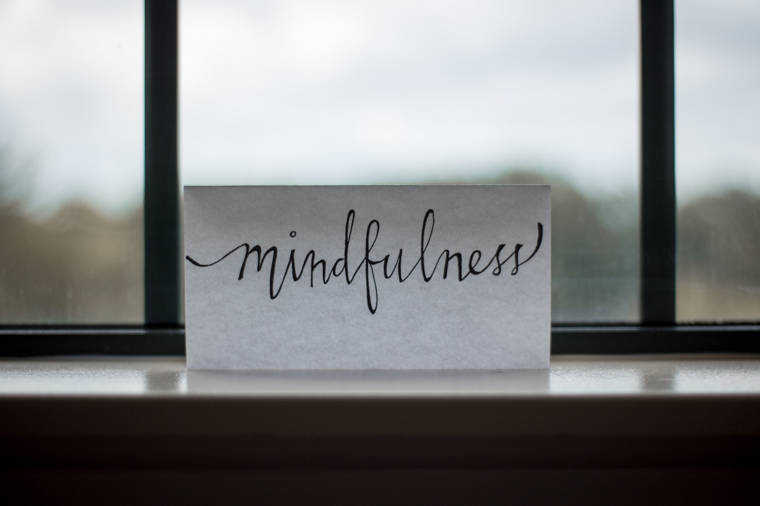 "A handwritten note reading ""mindfulness"" sits on a ledge in front of a misty window."