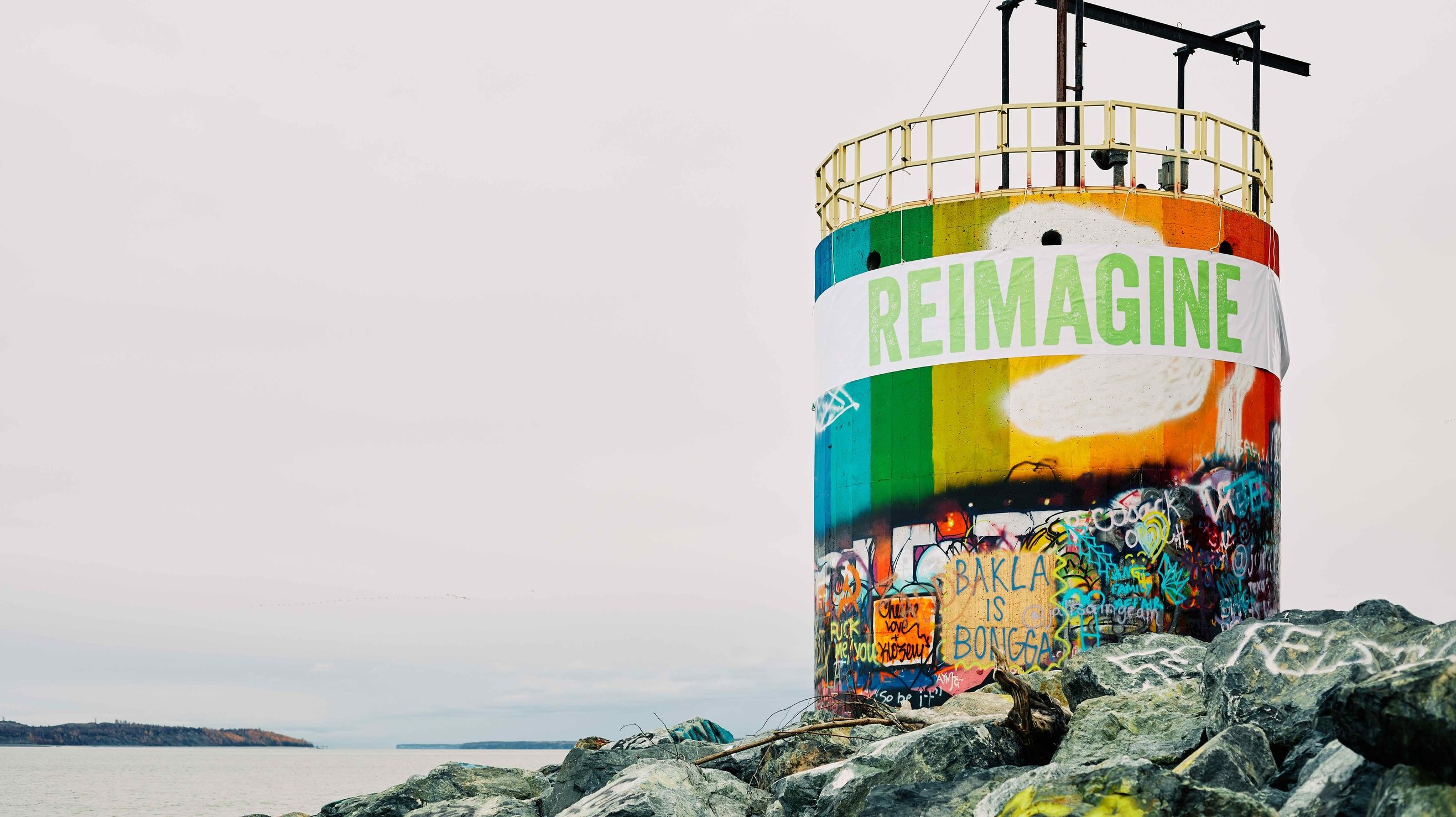 "A water tower with a mural drawn on it reading ""Reimagine"""