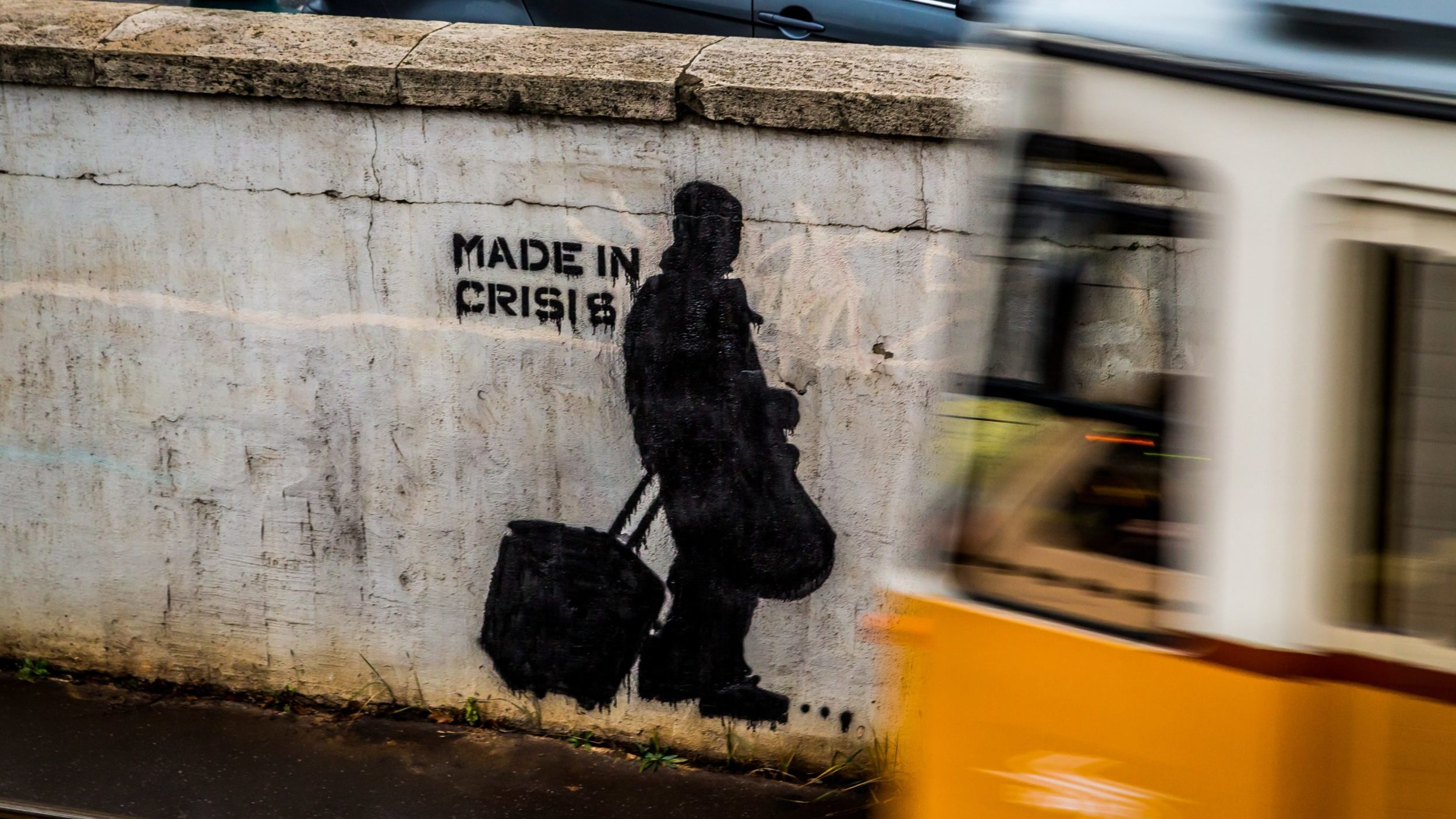 "Street art with a stencil of a person walking with bags and the words ""Made in Crisis."""