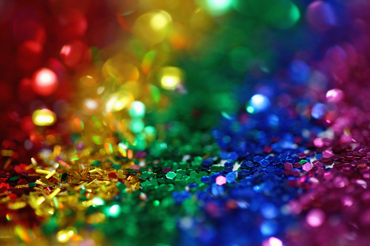 Whimsical and colorful rainbow glitter background.