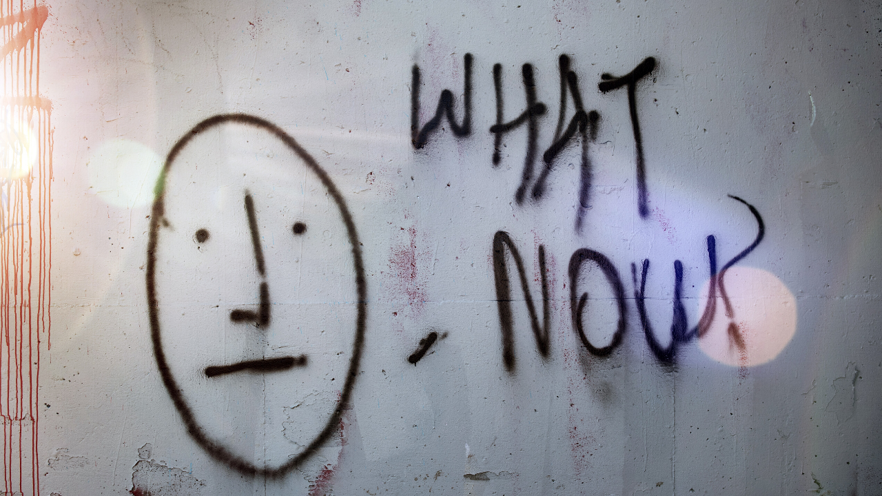 "Graffiti reading ""What Now"" with a drawing of an uncertain face."
