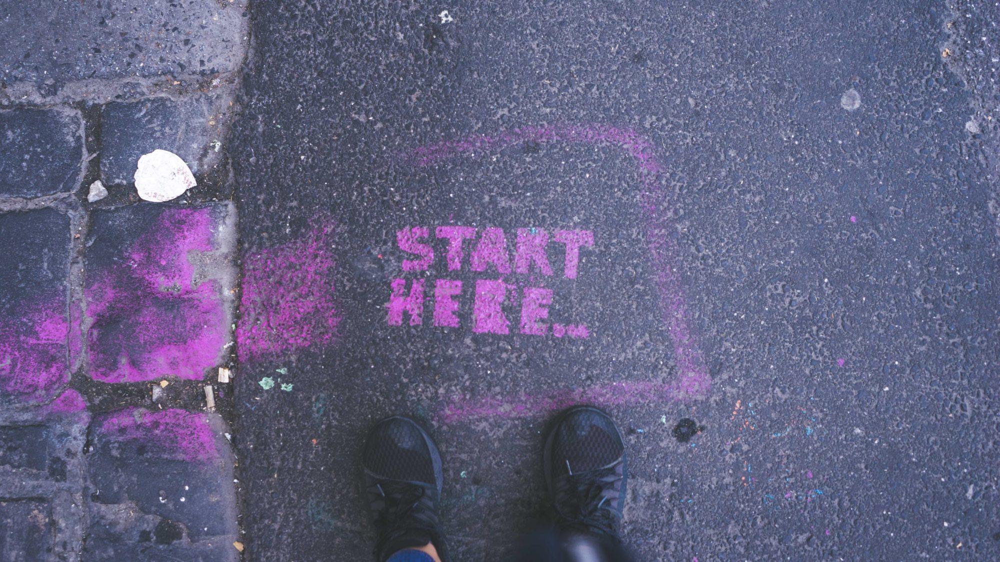 "Sneaker-wearing feet standing over sidewalk art reading ""Start here..."""
