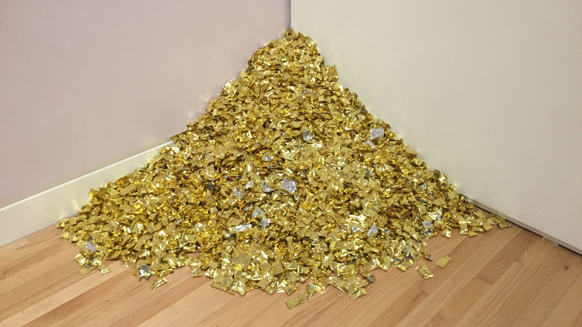 A small mountain of gold-wrapped candies in the corner between two walls