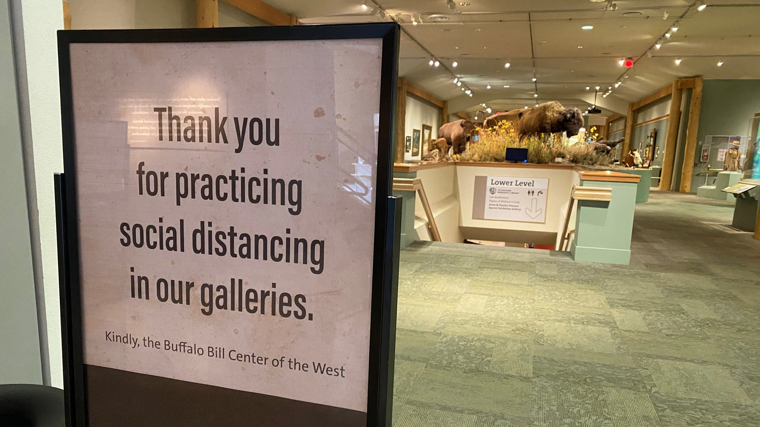 "Inside of a museum lobby, a sign reading, ""Thank you for practicing social distancing in our galleries. Kindly, Buffalo Bill Center of the West."