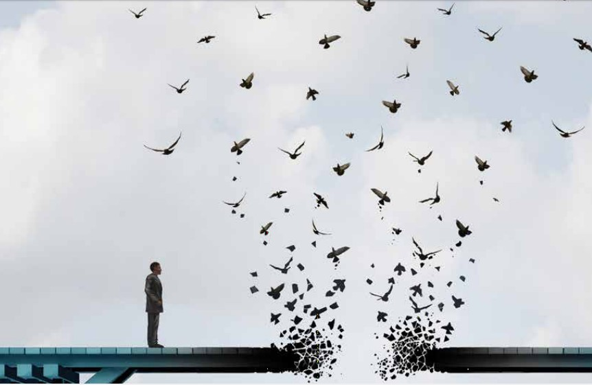 A man stands on a wooden bridge with a break in the middle where dozens of birds are flying off into space.