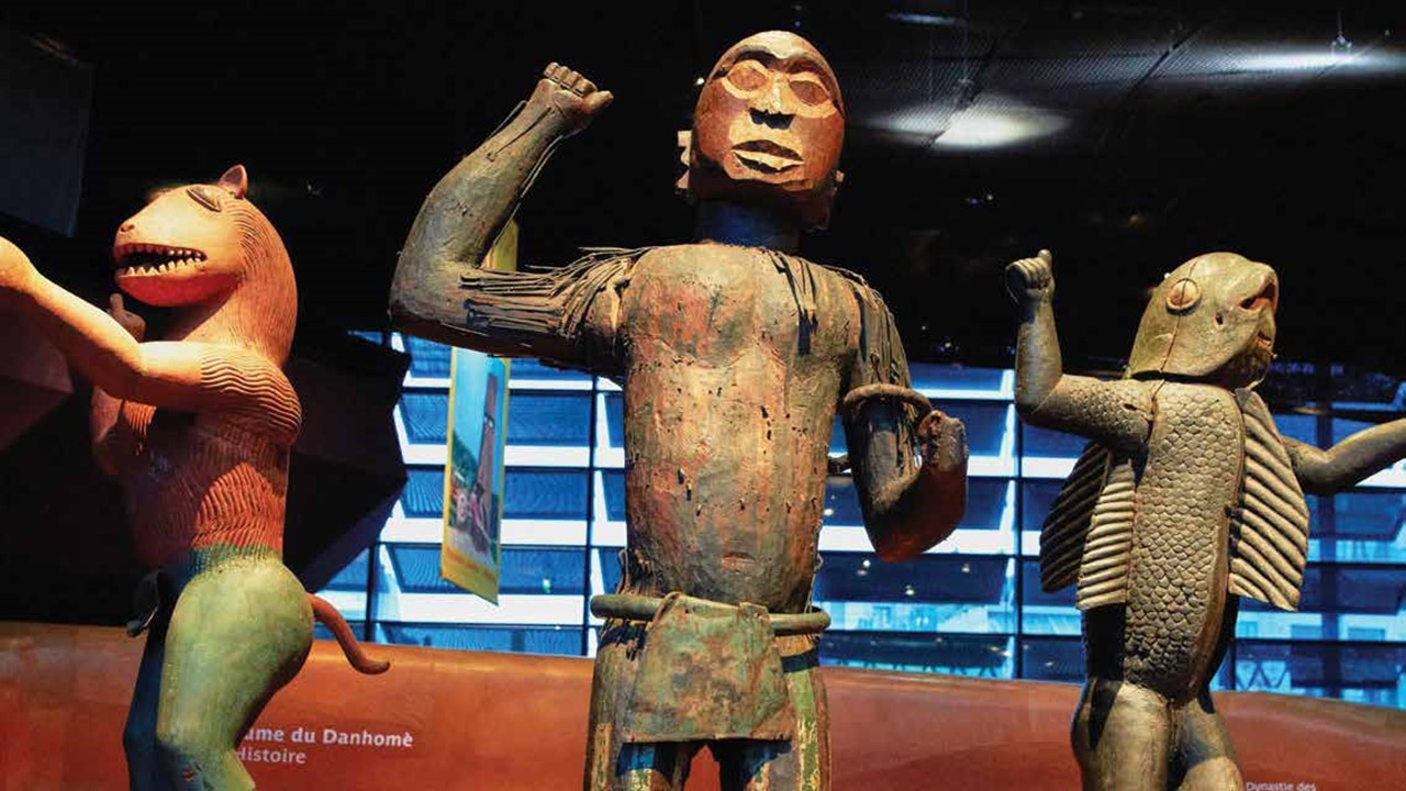 Three Benin bronze statues stand in a museum exhibition.
