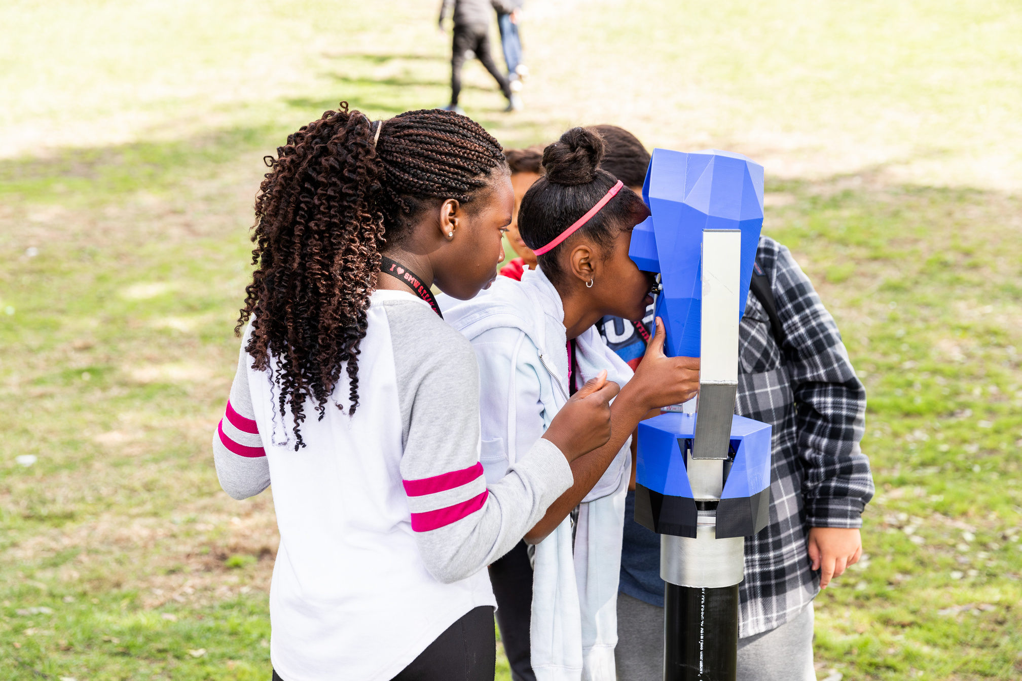 Children looking into a blue device resembling a periscope