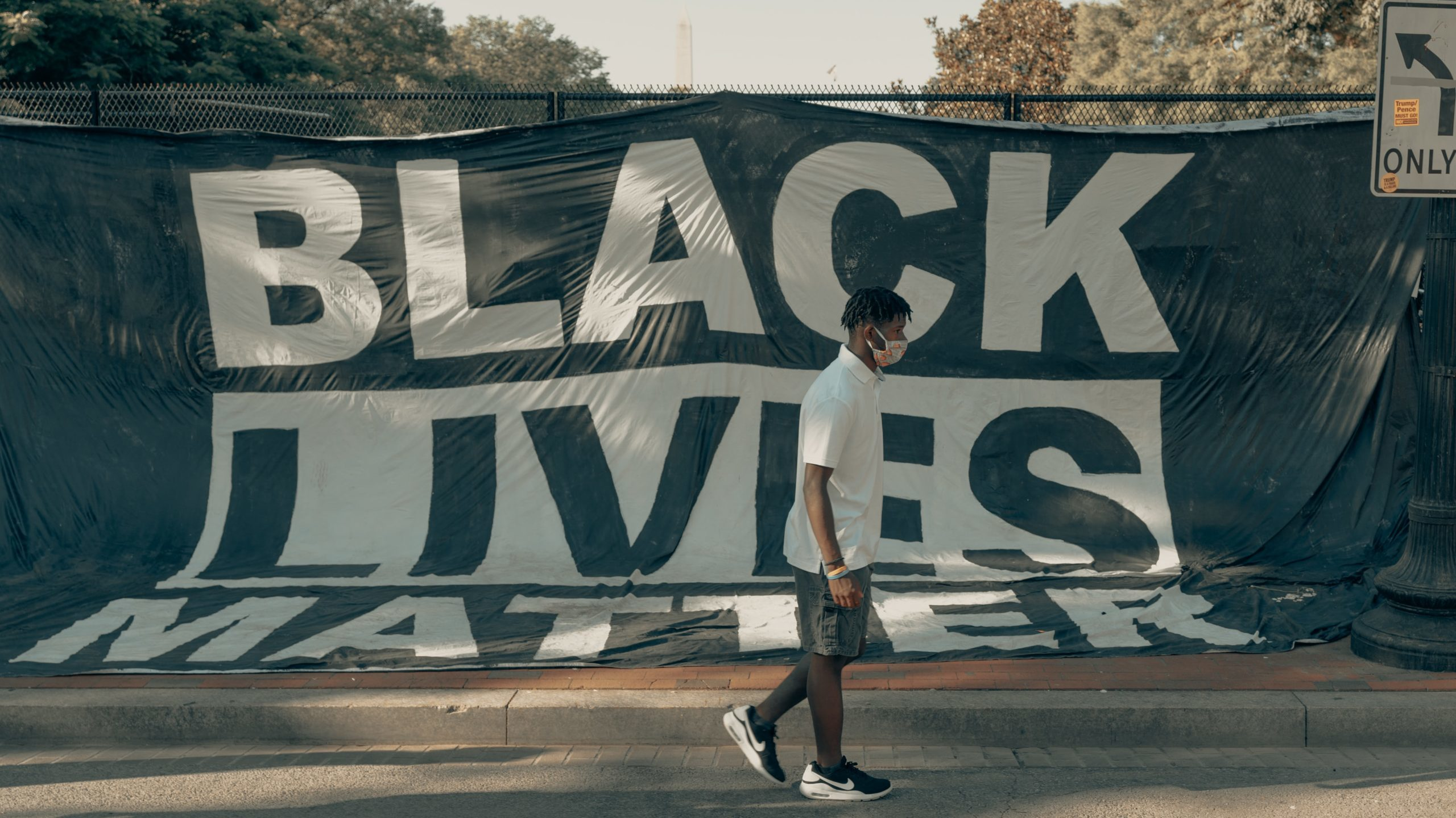 A teenager wearing a face mask walking past a Black Lives Matter banner hung on a fence