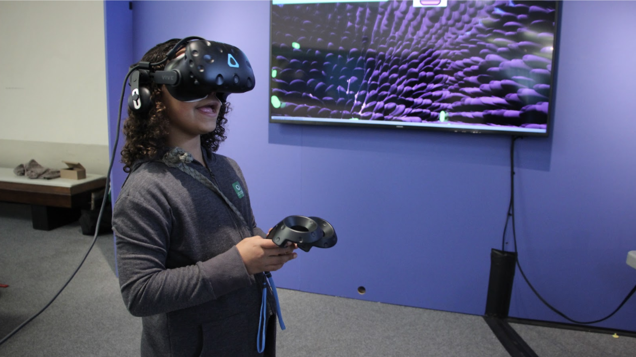 picture of girl wearing VR headset holding game controller