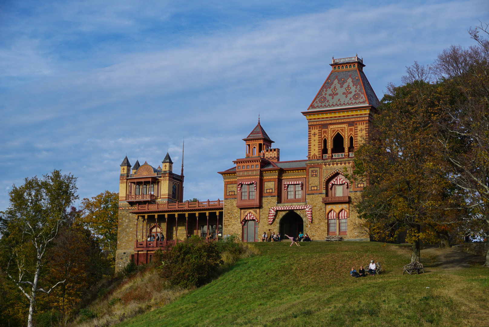 An exterior of a large historic house perched on a hill