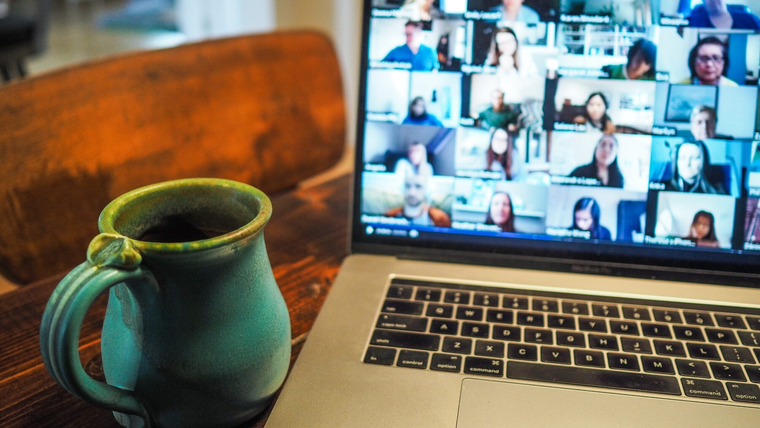 A laptop open to a Zoom conversation with a mug in the foreground