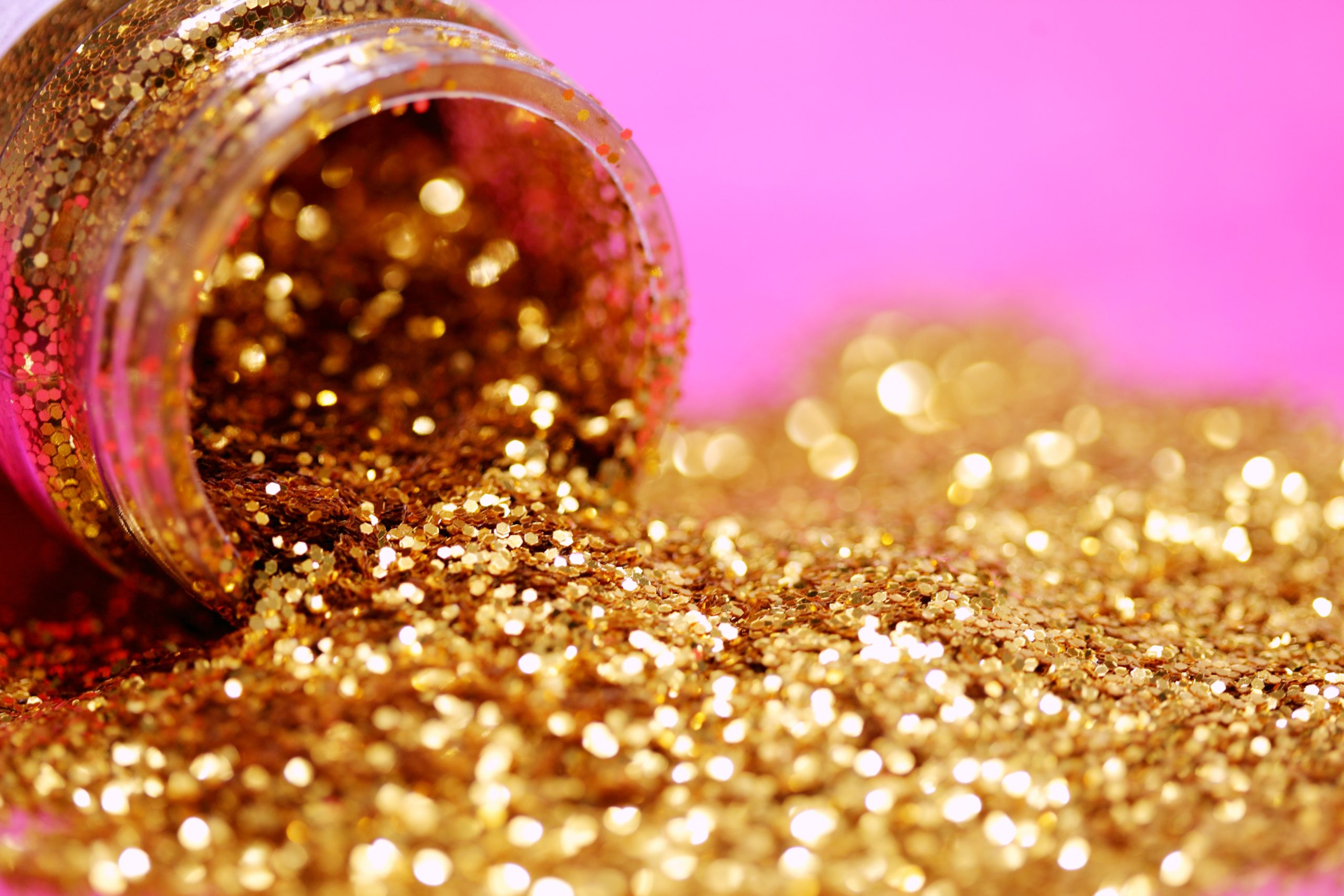 A bottle of gold glitter poured out against a pink background.