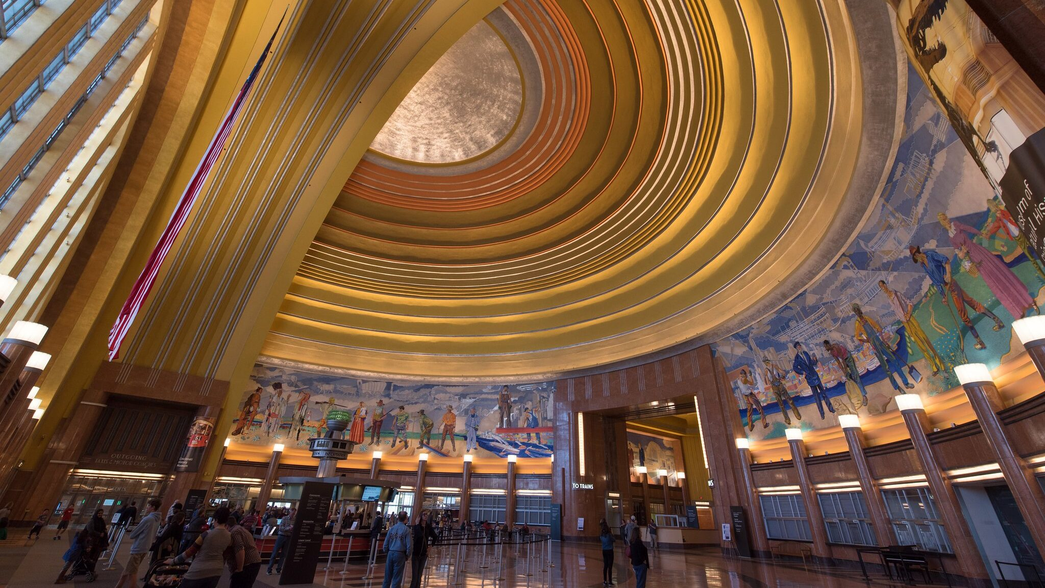 Interior of a curving Art Deco building with a museum ticket queue visible