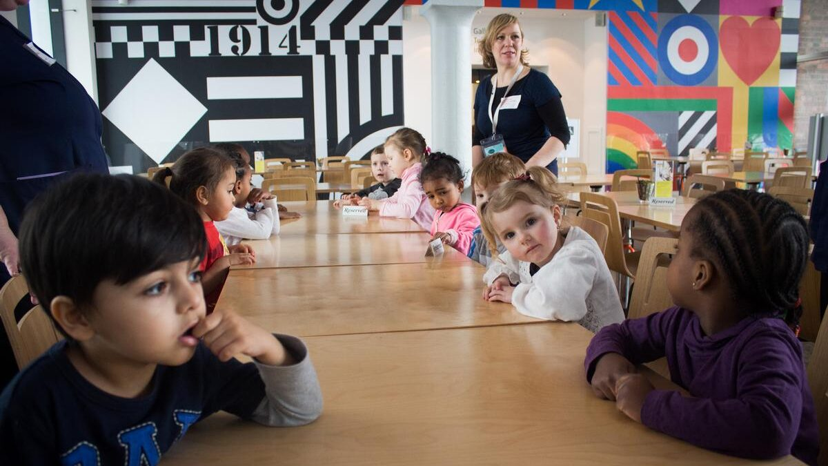 Children sitting around tables in front of graphic wall murals, with a teacher standing in the background