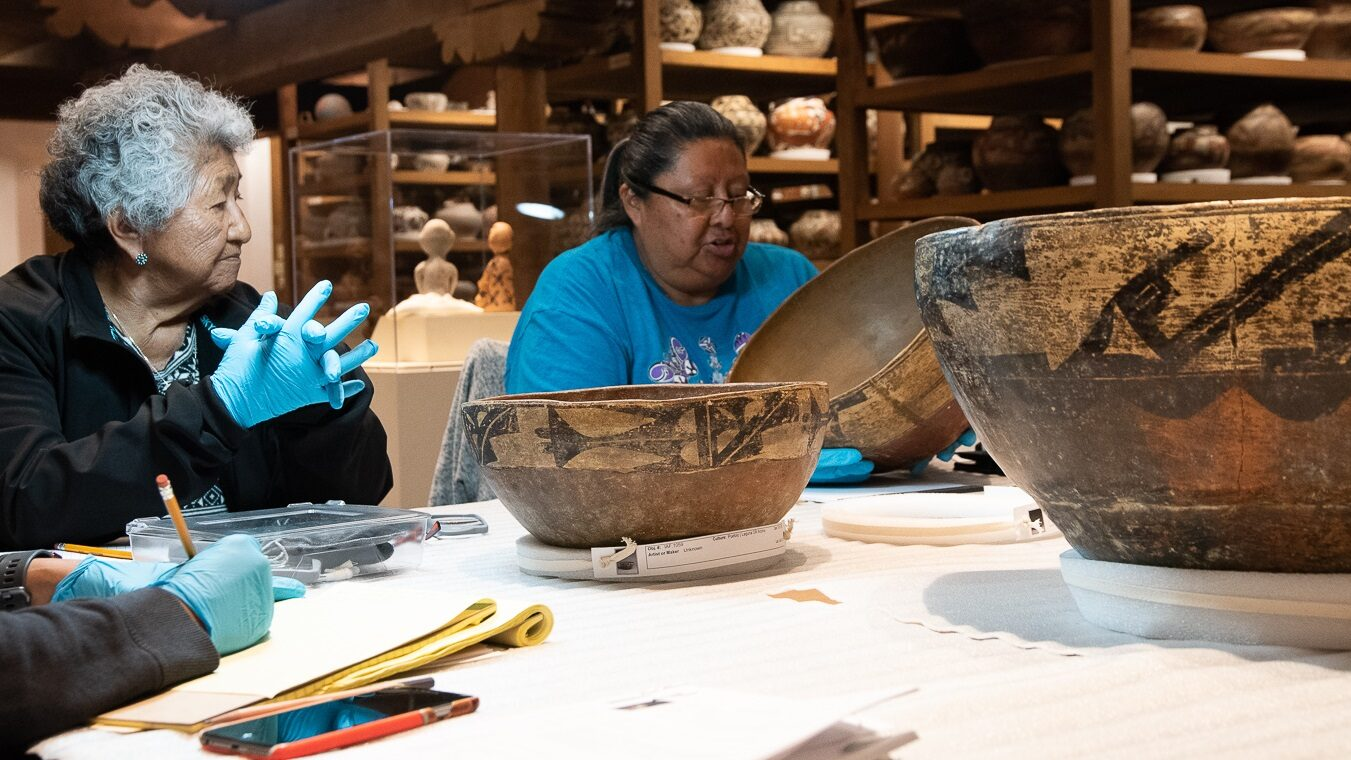 People sitting around a table wearing gloves and looking at Native pottery