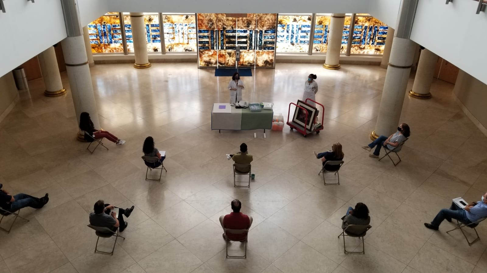 Aerial view of people sitting spaced out and wearing masks in a museum setting