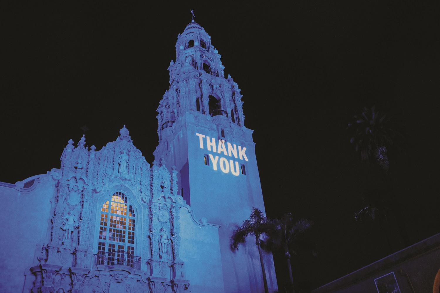 "An exterior shot of the Museum of Us with ""Thank You"" projected onto the facade."