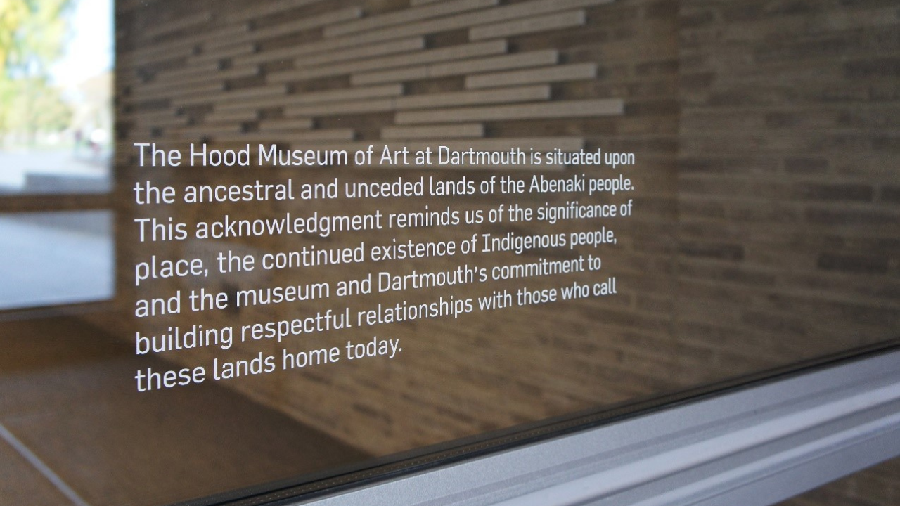 "A decal on a window reading ""The Hood Museum of Art at Dartmouth is situated upon the ancestral and unceded lands of the Abenaki people. This acknowledgment reminds us of the significance of place, the continued existence of Indigenous people, and the museum and Dartmouth's commitment to building respectful relationships with those who call these lands home today."""