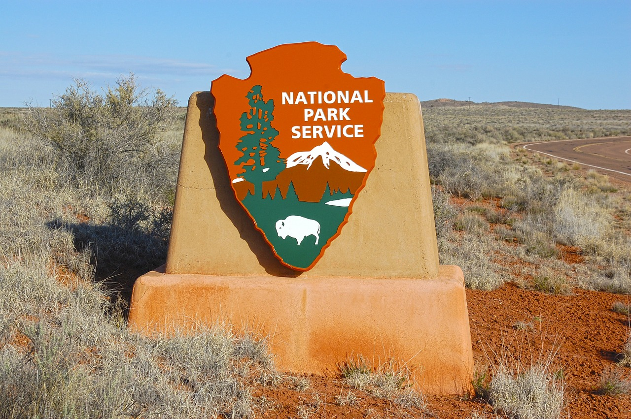 A sign with the National Park Service logo on it, in from of a desert landscape