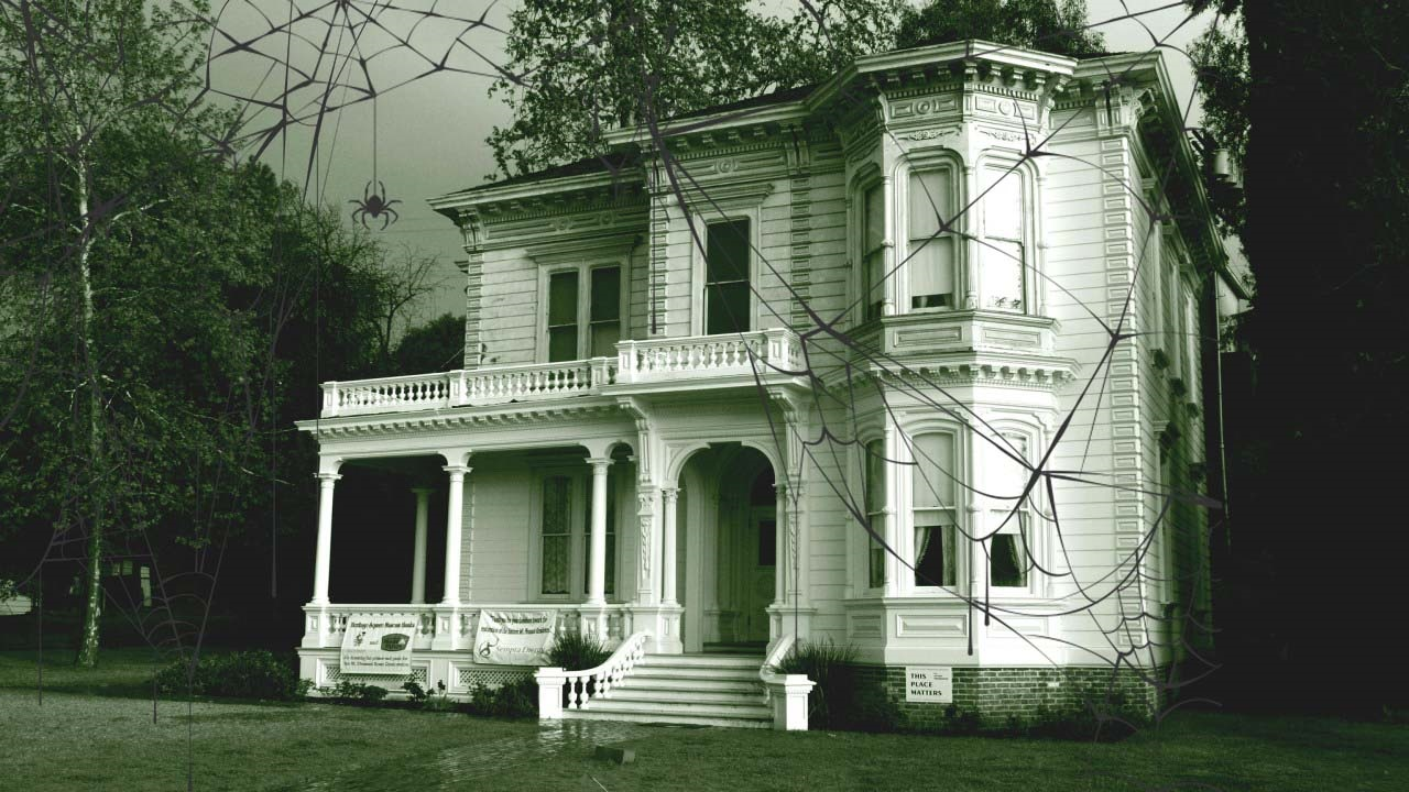 A sepia-colored photograph of a Victorian mansion