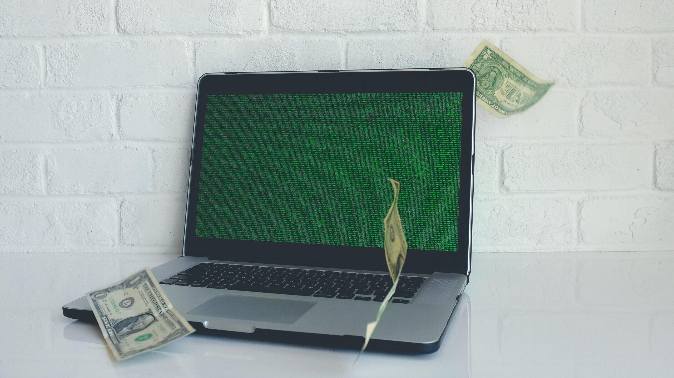 A laptop with dollar bills raining down on it
