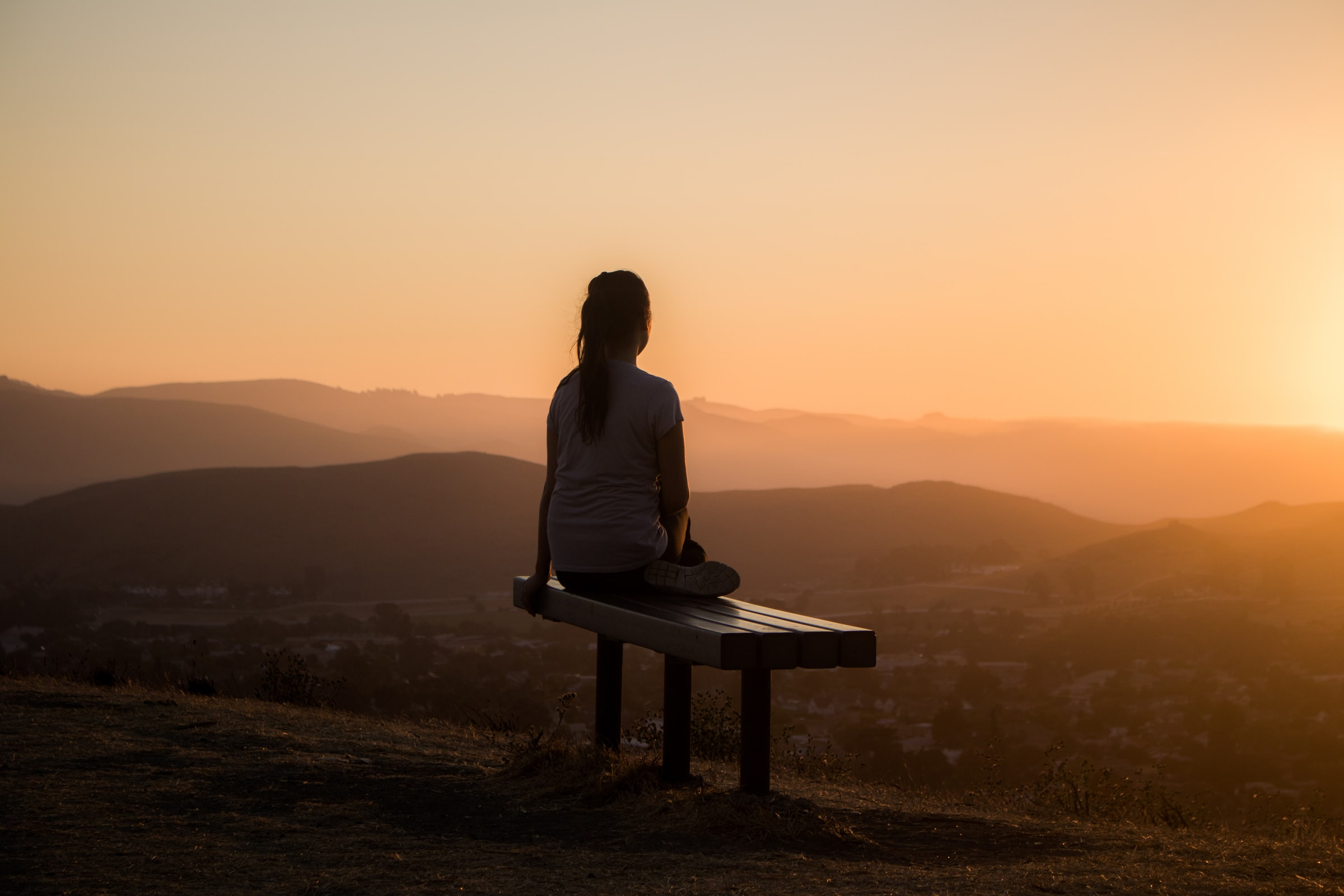 A person sitting on a bench looking down at mountains at sunset