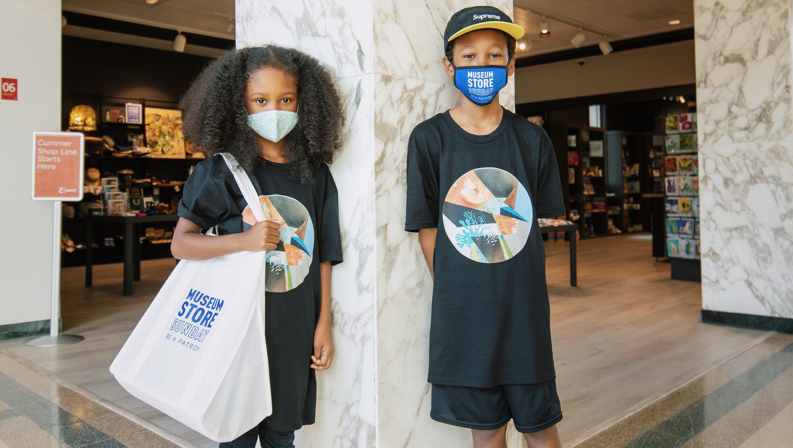 "Children posing in a museum space wearing ""Museum Store Sunday"" branded tote bags and face masks."