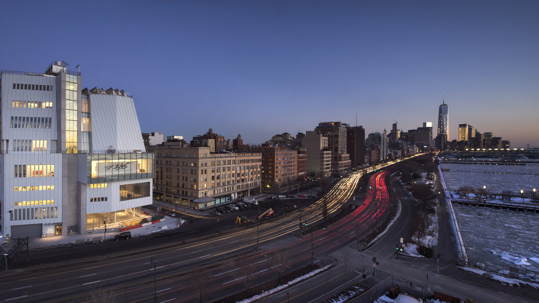 An exterior of the Whitney Museum building at sunset, with a view of the Hudson River nearby