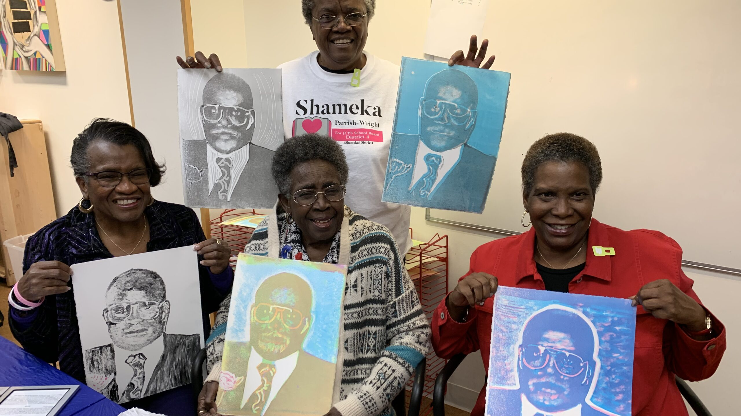A group of people holding up pop art portraits of a Black man