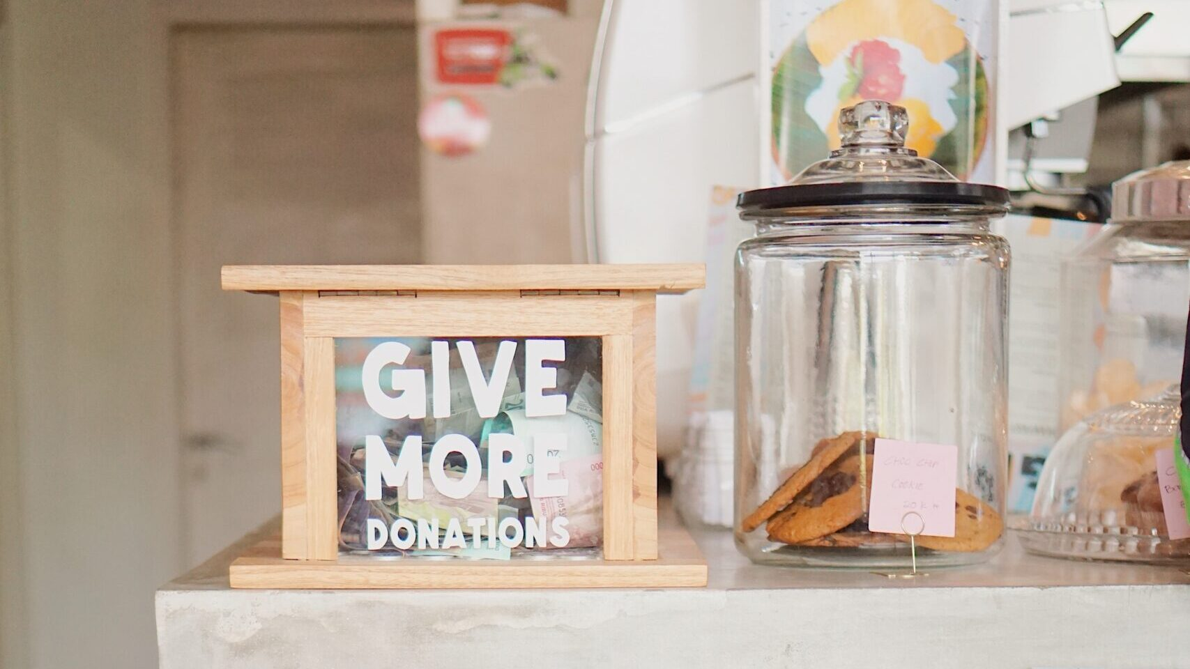 """A collection of tip jars with the message """"Give More Donations"""" written on one."""