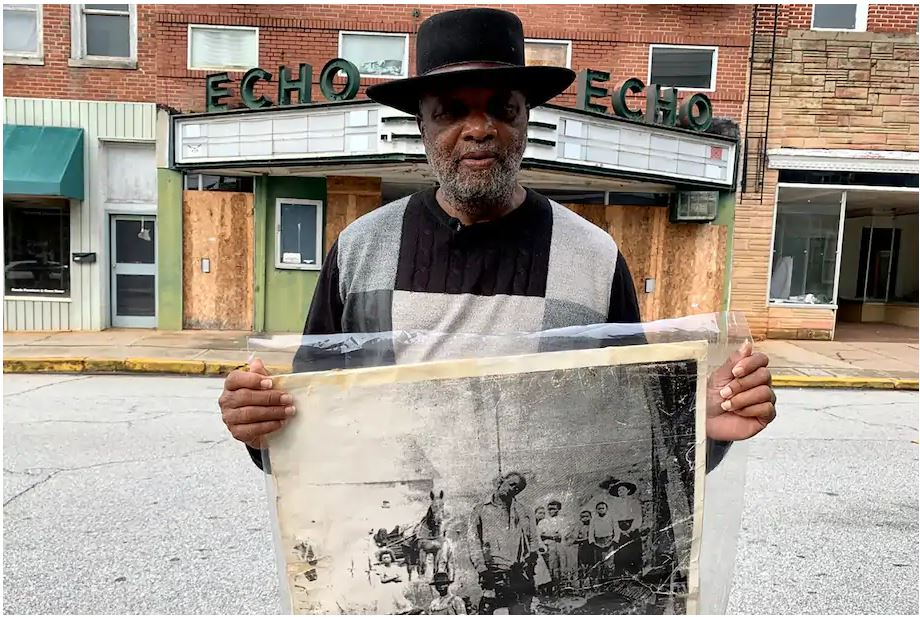 The Rev. David Kennedy, seen outside the Echo Theater in Laurens, S.C., holds a photo of his great-great-uncle's lynching. Kennedy has fought for civil rights in South Carolina for decades. (Sarah Blake Morgan/AP)