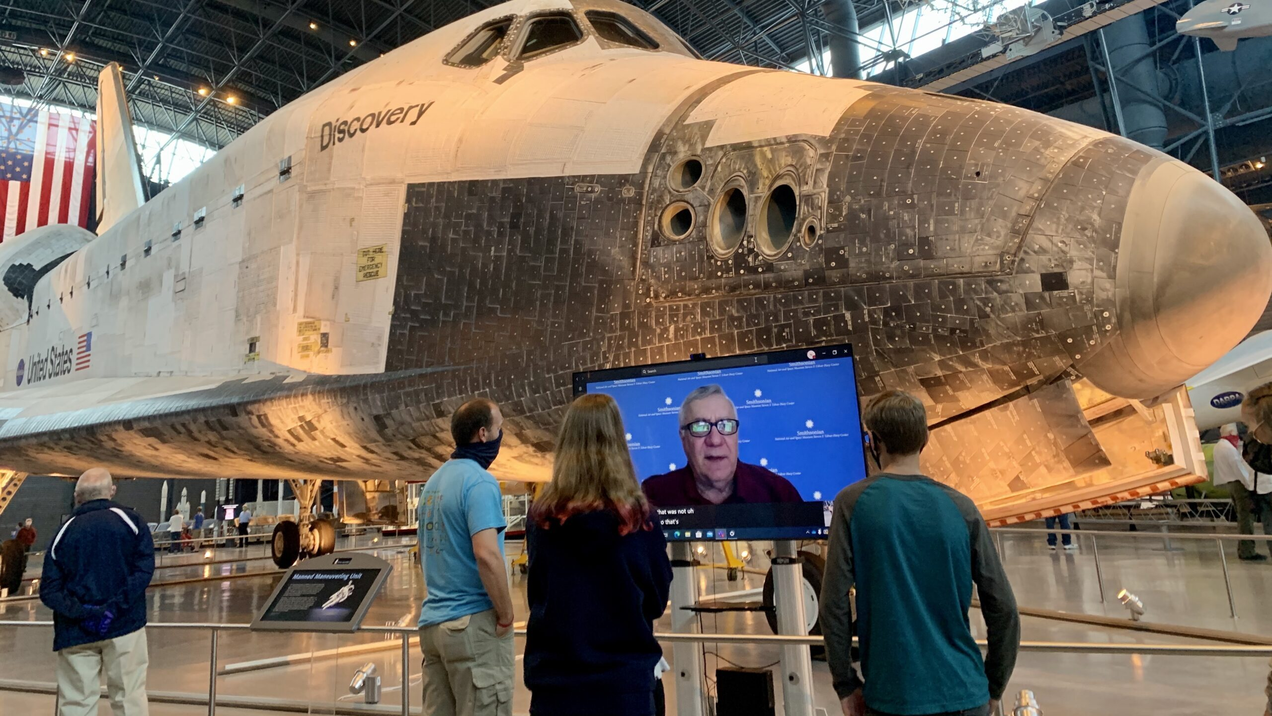 A group of people stand in front of a video screen with a feed of a volunteer speaking, with an artifact plane visible in the background