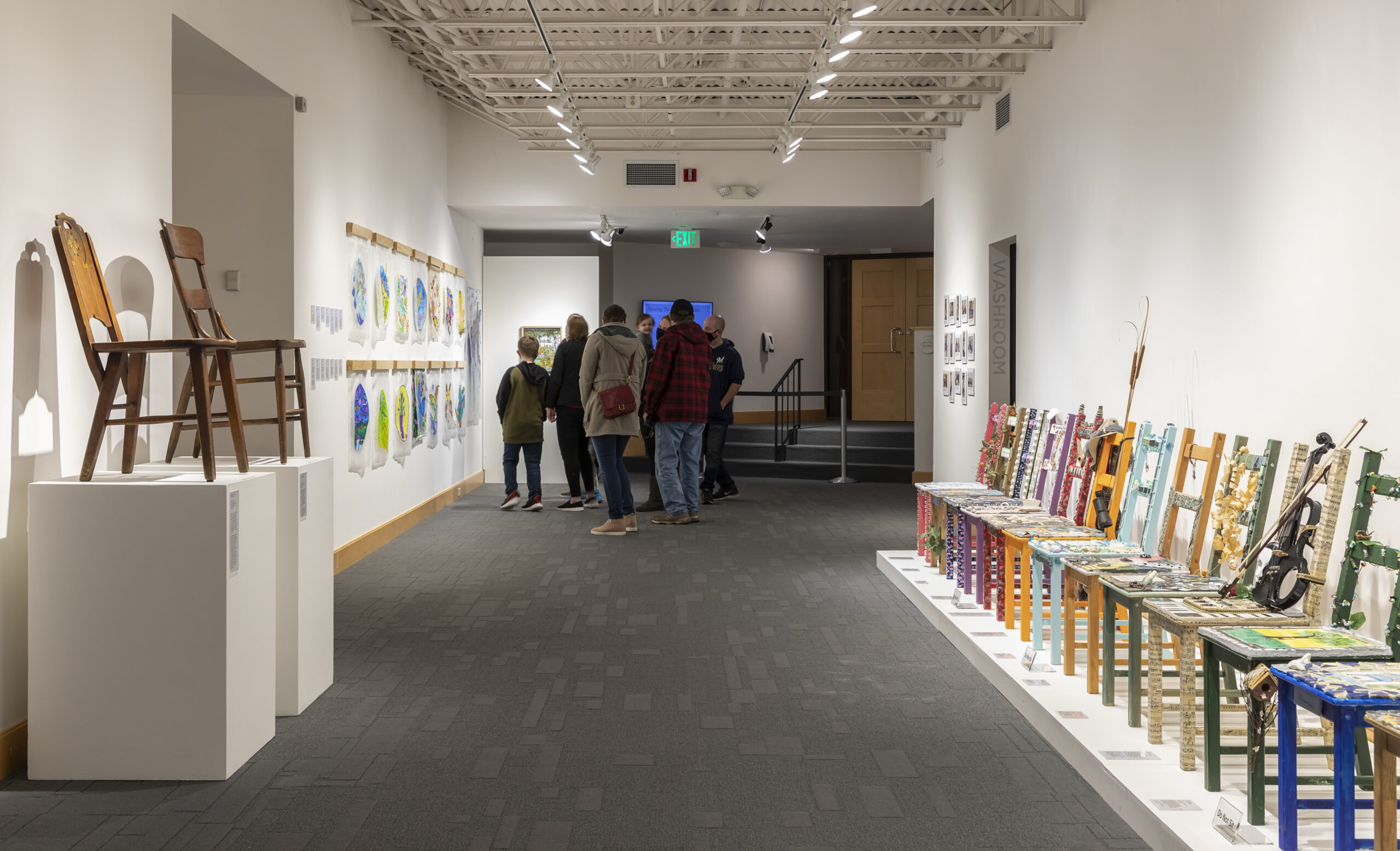 A gallery of decorative chairs and wall hangings with a huddle of visitors looking at them