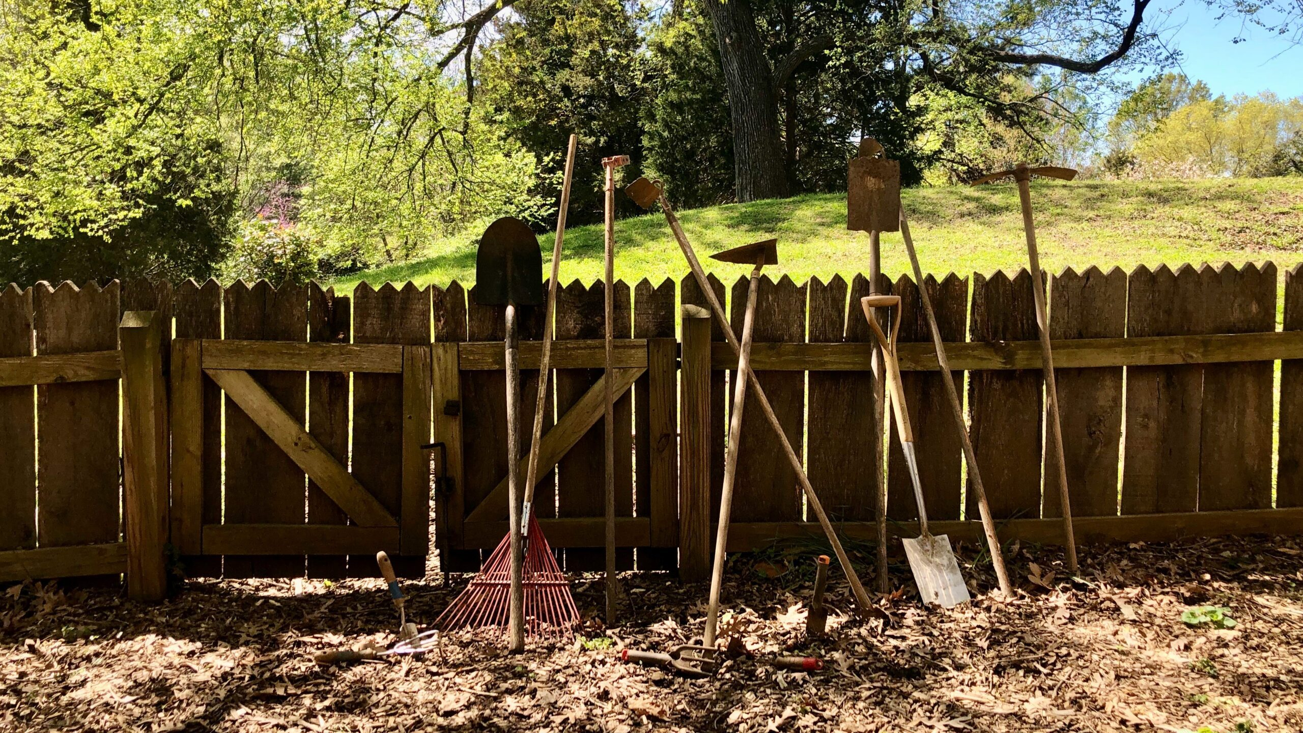 Gardening tools leaned against a wooden fence