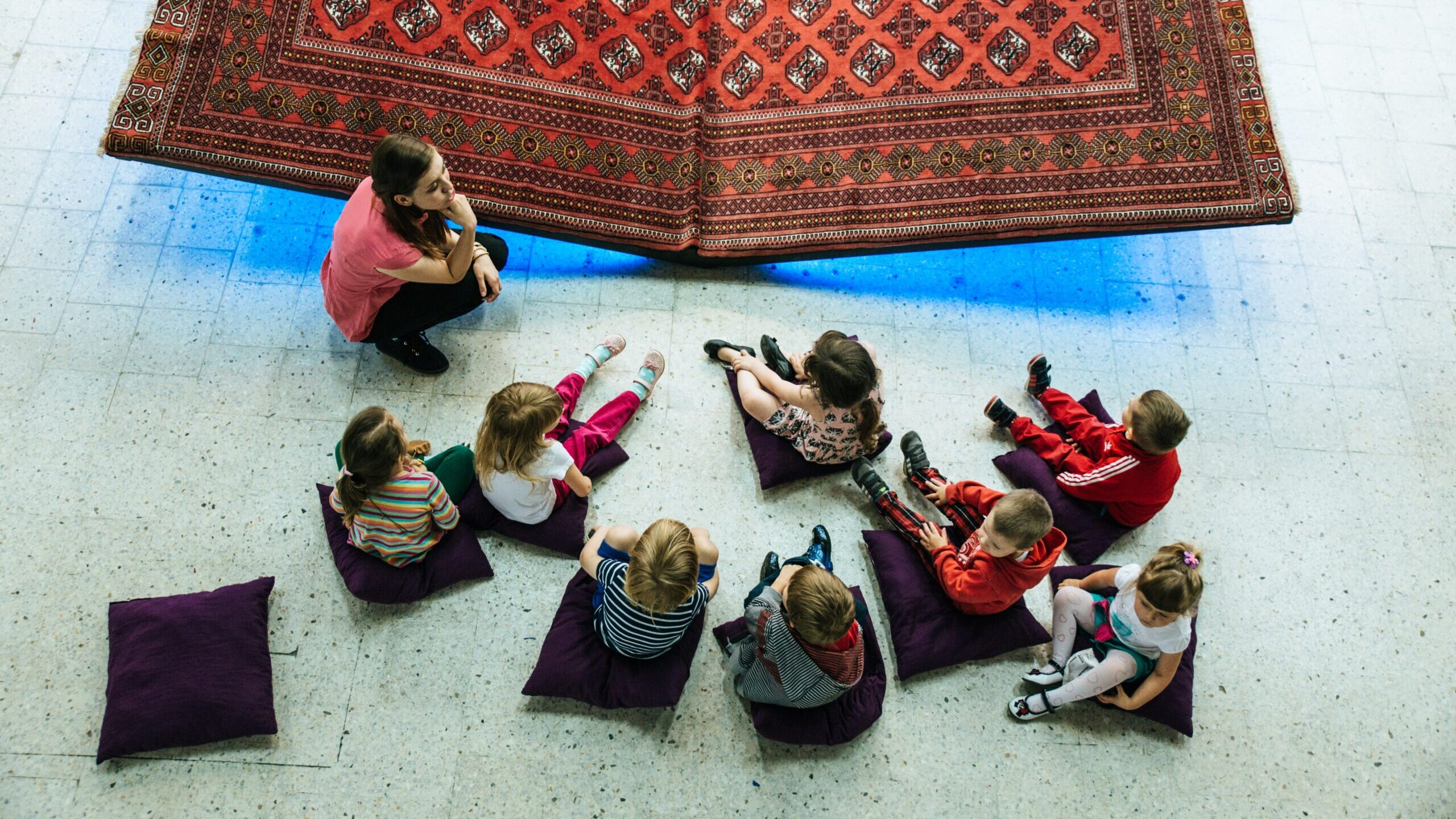 A museum educator leading a discussion with a group of children on the floor in front of a work of art