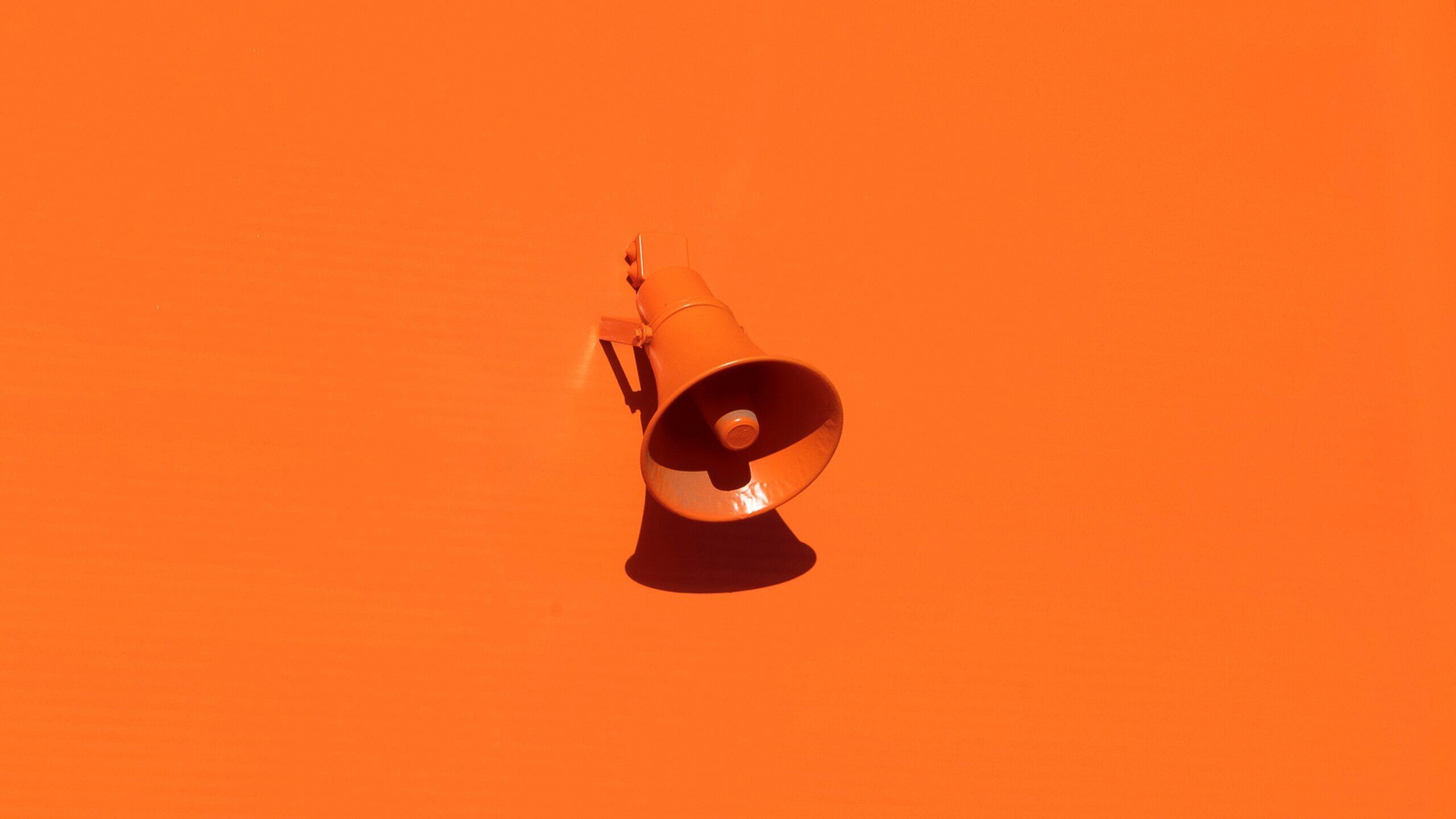 An orange megaphone on an orange background