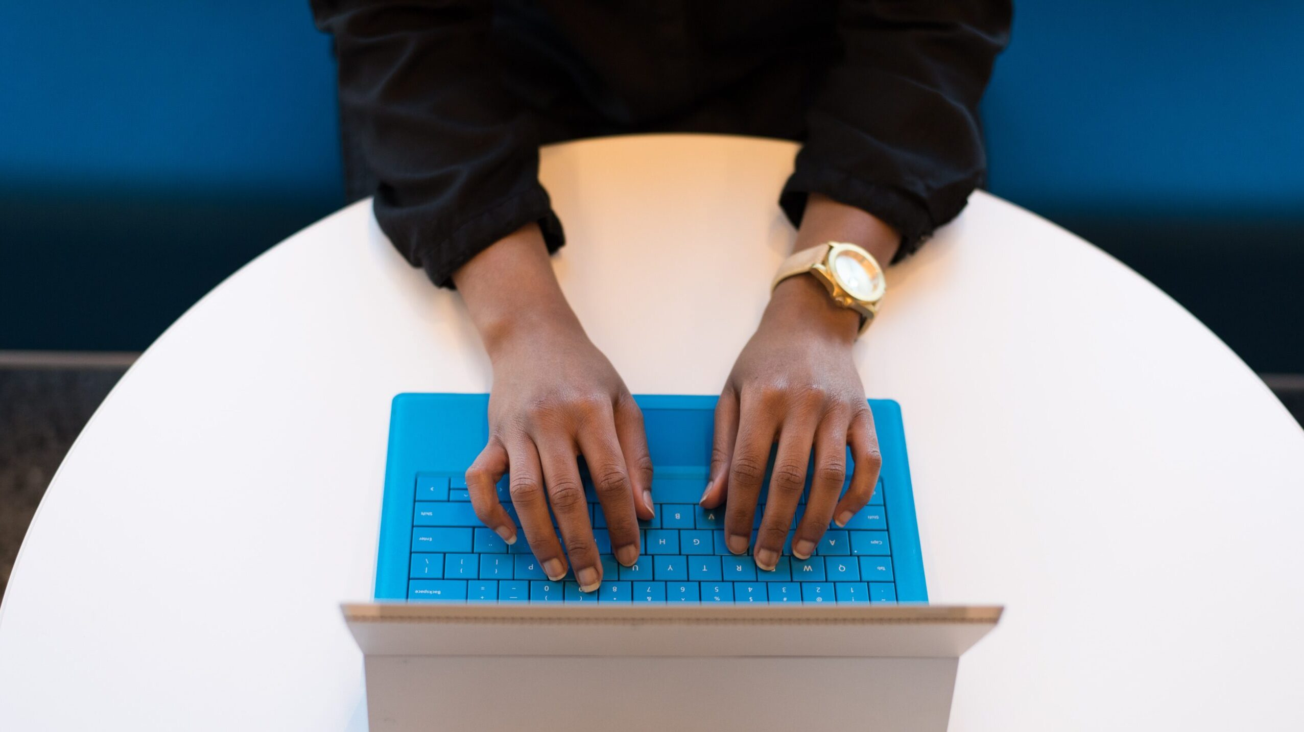 a person seen from above typing on a laptop with a blue keyboard
