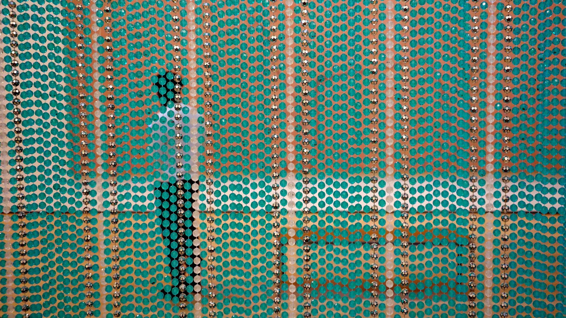 A visitor standing in a gallery looking at a painting seen through a colorful bead curtain