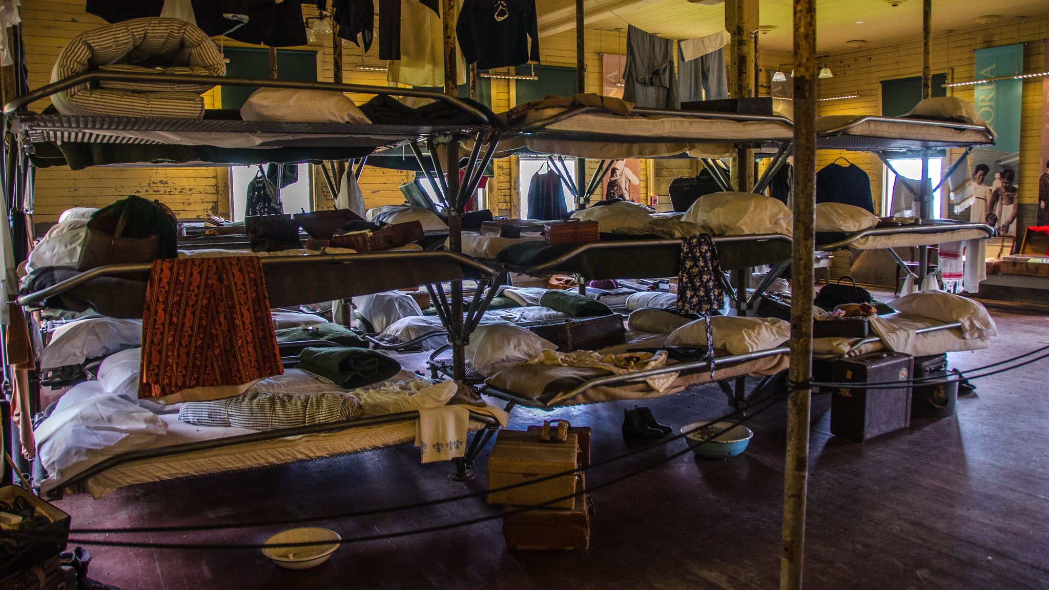 A row of bunk beds draped in clothing and other personal possessions, roped off inside a museum space.