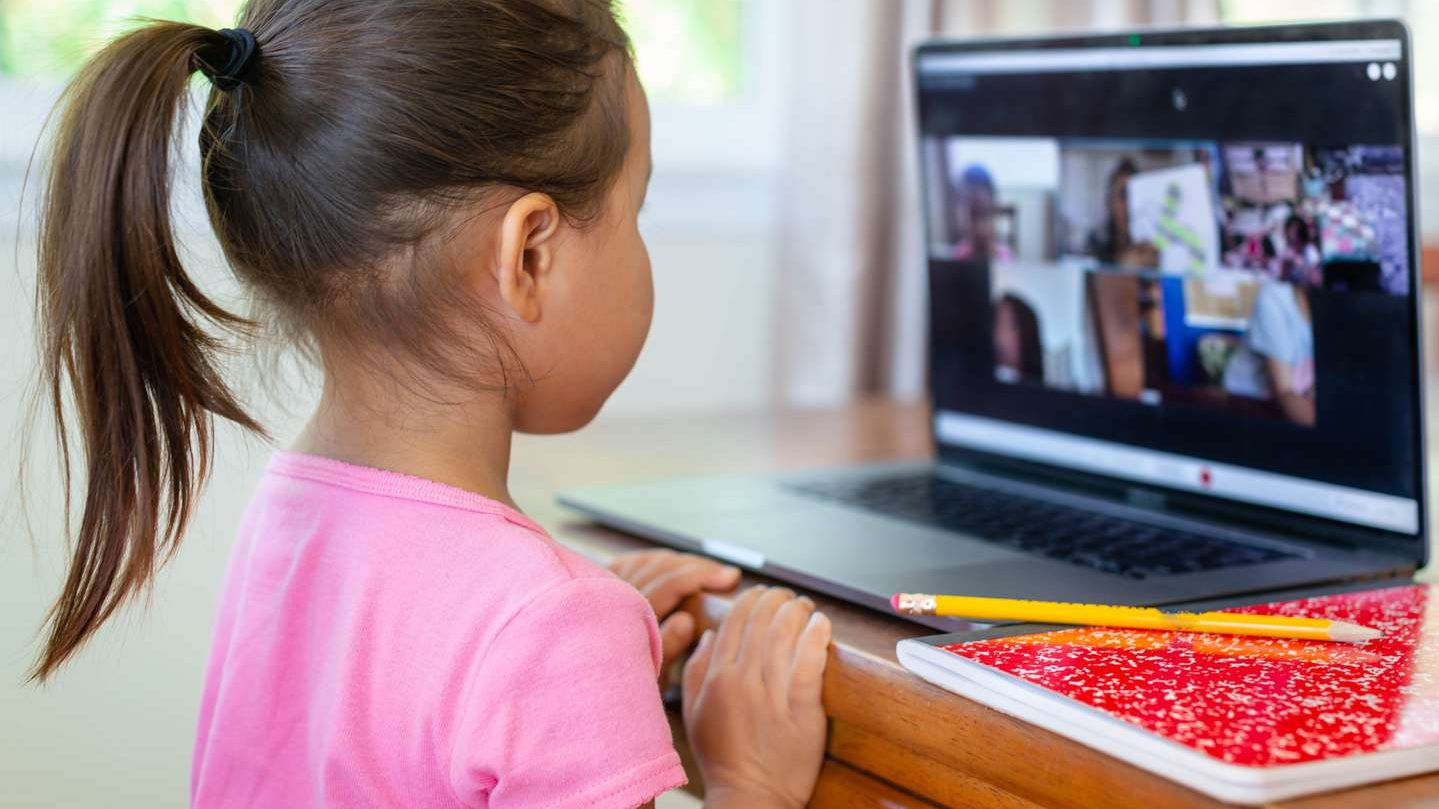 A child watching a video meeting on a laptop screen