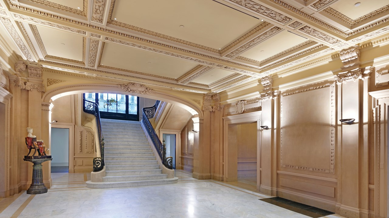 The interior of a large grand hall with decorative molding on the walls and ceiling and a split stairway with marble flooring at the far end.