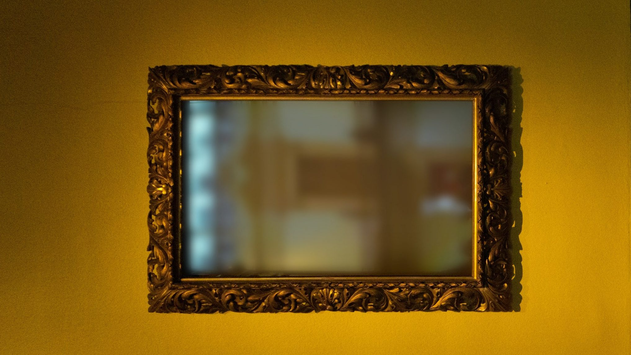 A framed mirror on a yellow gallery wall with a hazy reflection of a museum interior