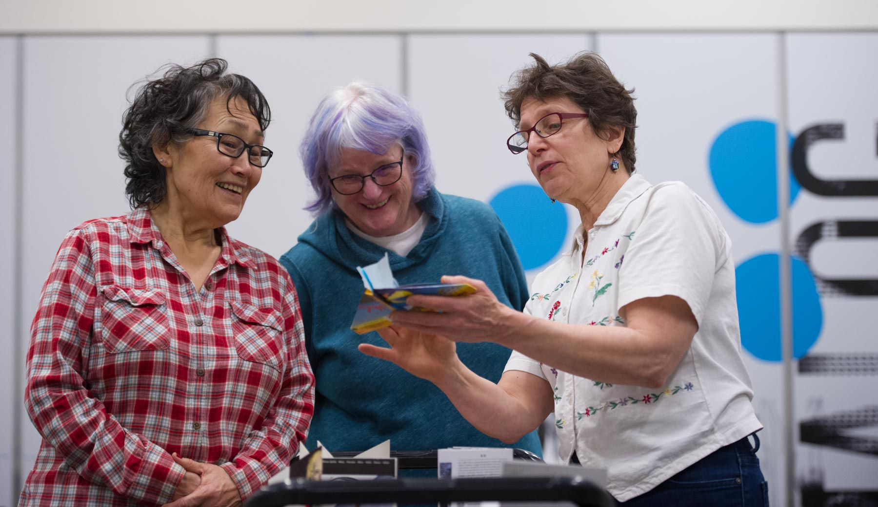 A group of people looking at an art project and smiling